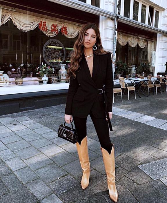 menina de cabelos castanhos vestindo jaqueta blazer preta, jeans skinny preto, botas longas marrons e uma pequena bolsa preta