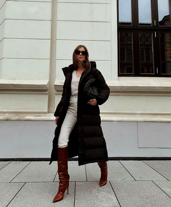 menina de cabelos castanhos usando óculos escuros, top branco com decote em V, paletó preto longo, jeans branco, botas de couro marrom com salto e bolsa preta