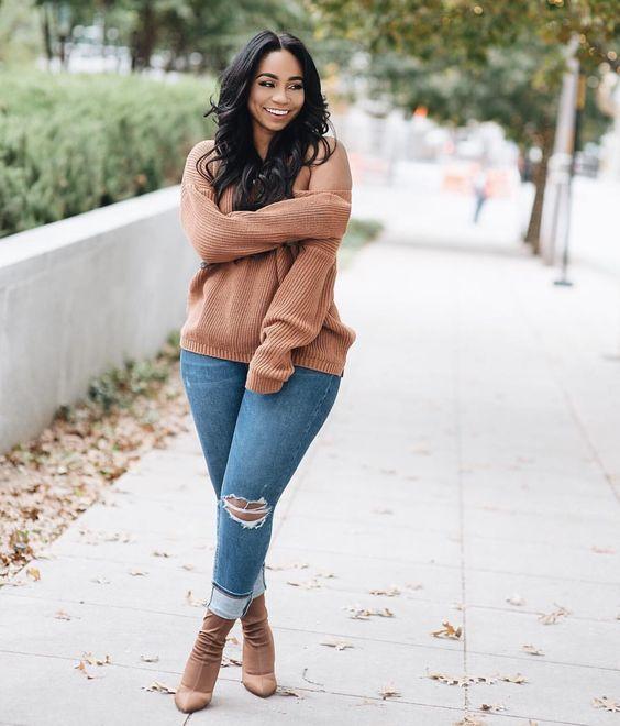 mulher com suéter marrom e calça jeans