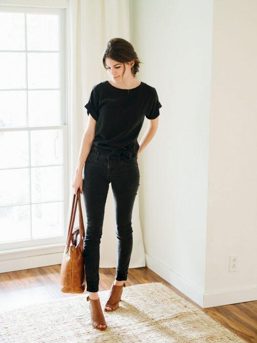 Mulher vestida de preto, bolsa e sapatos marrons