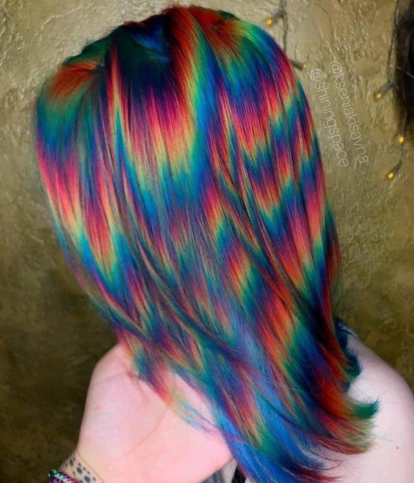 Mulher com cabelo curto pintado em cores extravagantes que parecem flashes de luz, rosa, laranja, amarelo, verde e azul
