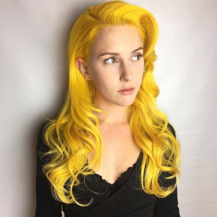 Menina sem maquiagem, olhos verdes, cabelos longos e ondulados tingidos de amarelo canário