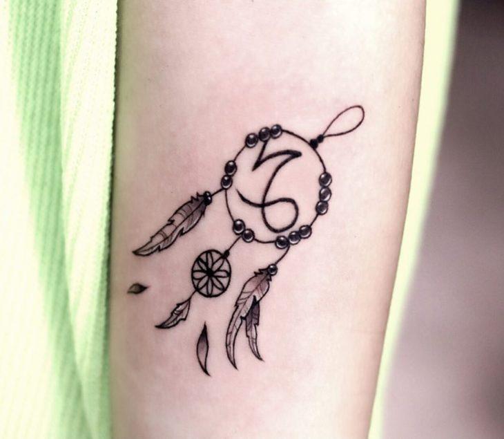 Tatuagem do símbolo de Capricórnio e um apanhador de sonhos na área do antebraço