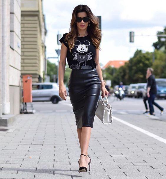 Menina andando pela rua vestindo roupa com saia lápis e blusa estampada do Mickey Mouse