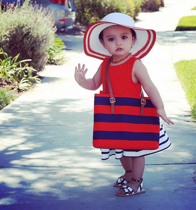 Menina mini fashionista com vestido vermelho, bolsa listrada de azul e vermelho e chapéu branco