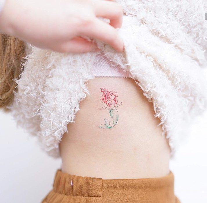 Tatuagem minimalista de Ariel da Pequena Sereia da Disney nas costelas