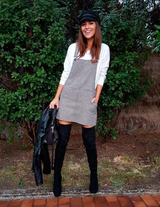 Menina com vestido avental cinza com botas e boina pretas