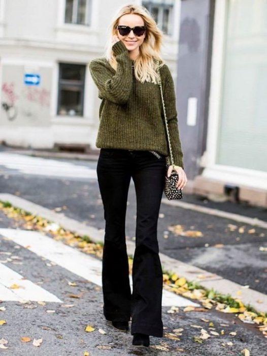 menina loira com calça boca de sino preta e suéter verde